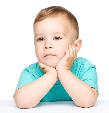 Portrait of a cute little boy sitting at table supporting his head with hands, isolated over white Stock Photo - 16695851