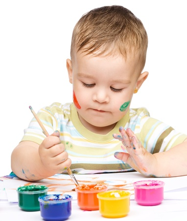 Portrait of a cute little boy messily playing with paints, isolated over white Stock Photo - 16695859