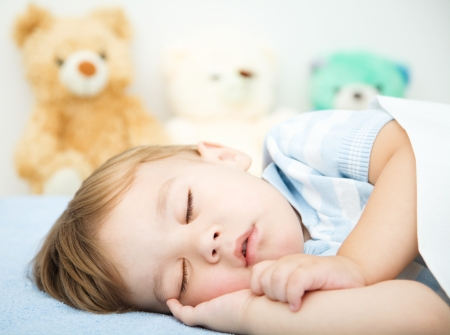 Cute little boy is sleeping in front of his teddy bears Banque d'images