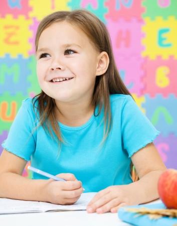 Cute little girl is writing using a pen in preschool Stock Photo - 16792091