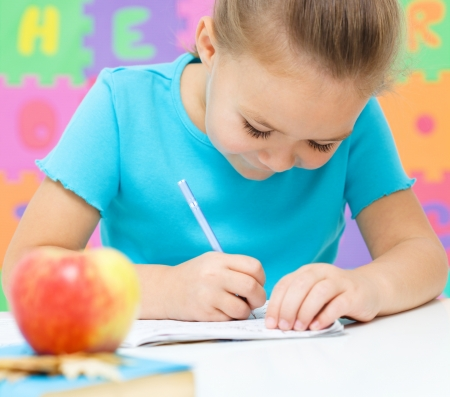 Cute little girl is writing using a pen Stock Photo - 16792117