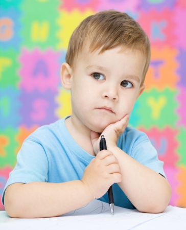 Little boy is writing on his copybook in preschool Stock Photo - 16792281