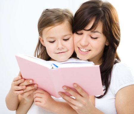 Mother is reading book with her daughter, indoor shoot photo