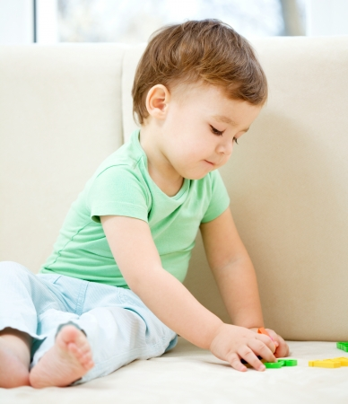 Cute little boy is playing while sitting on couch Stock Photo - 16792296