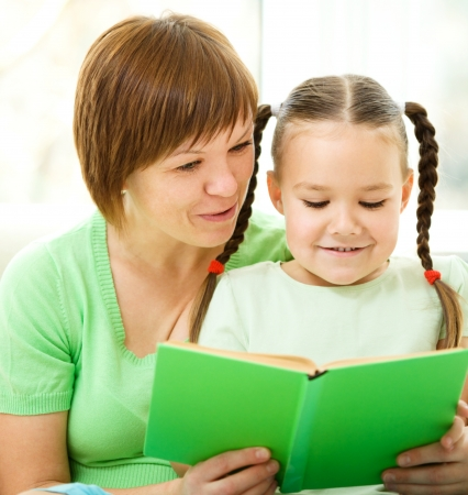 Mother is reading book with her daughter, indoor shoot Stock Photo - 16792290