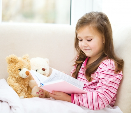Little girl is reading a story for her teddy bears while laying in bed and wearing pyjama, indoor shoot photo