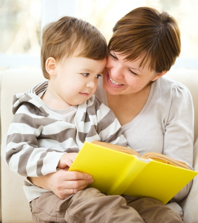 Mother is reading book for her son, indoor shoot Stock Photo - 16792291