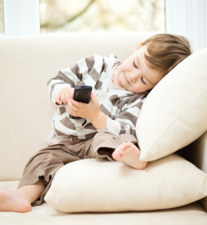 show off: Little boy is watching tv while sitting on a couch