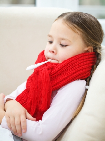 Ill little girl is laying on sofa with thermometer in her mouth Stock Photo - 16792089
