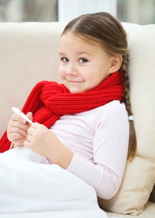 Ill little girl is reading thermometer while laying on sofa Stock Photo - 16792092