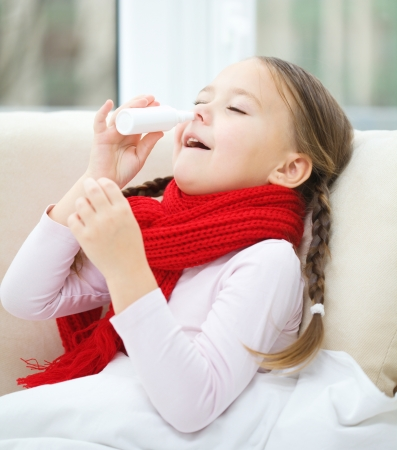 Little girl spraying her nose with nasal spray while sitting on sofa photo