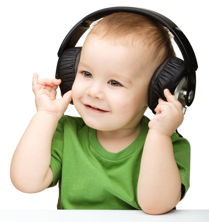 Cute little boy enjoying music using headphones, isolated over white Imagens