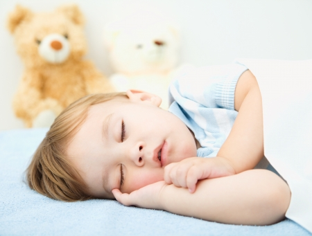 drowse: Cute little boy is sleeping in front of his teddy bears Stock Photo