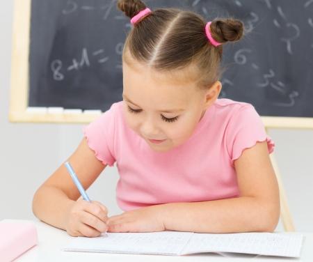 niños escribiendo: La niña linda está escribiendo con una pluma en el preescolar