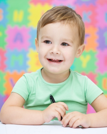 Little boy is writing on his copybook in preschool photo
