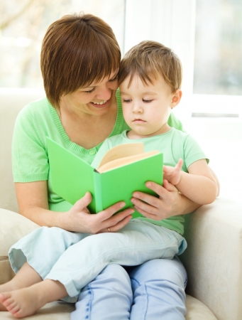 Mother is reading book for her son, indoor shoot photo