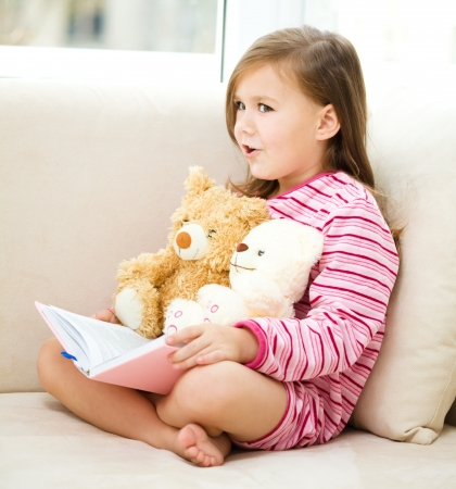 pajama: Little girl is reading a story for her teddy bears while laying in bed and wearing pajama, indoor shoot Stock Photo
