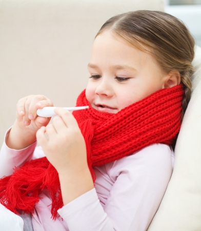 Ill little girl is reading thermometer while laying on sofa Stock Photo - 17107407