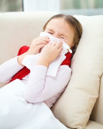 malady: Little girl is blowing her nose while sitting on a sofa