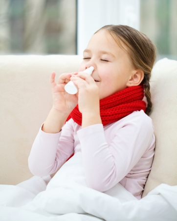 malady: Little girl spraying her nose with nasal spray while sitting on sofa
