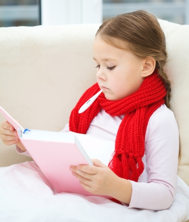 Ill little girl is sitting on sofa with thermometer in her mouth and reading book Stock Photo - 17107402