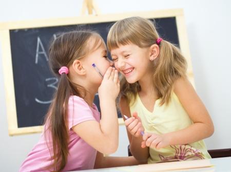 niños platicando: La niña linda está escribiendo con una pluma en la escuela