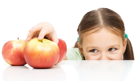 Cute little girl is reaching apple on table, isolated over white Imagens