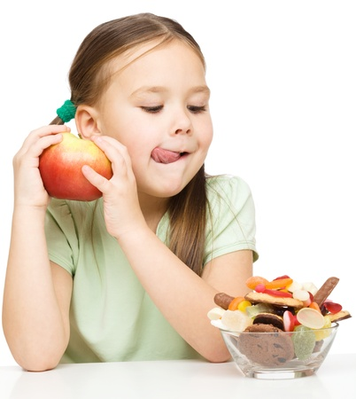 healthy choices: Cute little girl choosing between apples and sweets licking her lips, isolated over white
