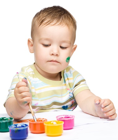 Portrait of a cute little boy messily playing with paints, isolated over white Stock Photo - 17055238