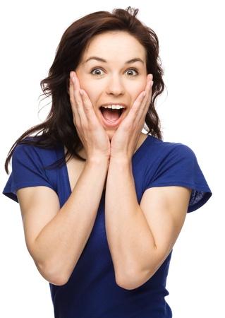 astonishment: Mujer joven está sosteniendo su cara de asombro, aislado más de blanco