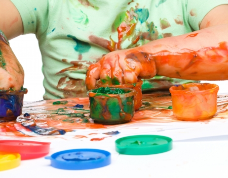 Portrait of a cute little boy messily playing with paints, isolated over white Stock Photo - 17055223