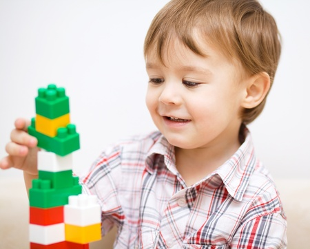 Cute little boy is playing with building blocks Stock Photo