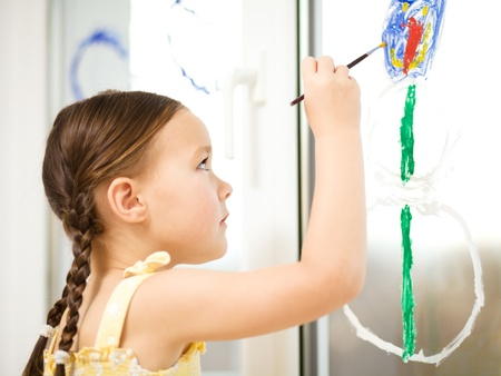 Portrait of a cute cheerful girl playing with paints on window Stock Photo - 17134304