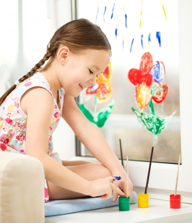 Portrait of a cute cheerful girl playing with paints on window Stock Photo - 17134303