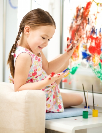 Portrait of a cute cheerful girl playing with paints on window Stock Photo - 17134314