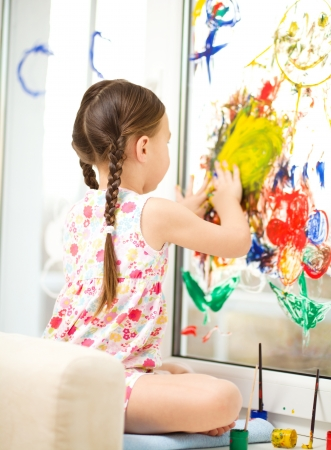 Portrait of a cute cheerful girl playing with paints on window Stock Photo - 17134315