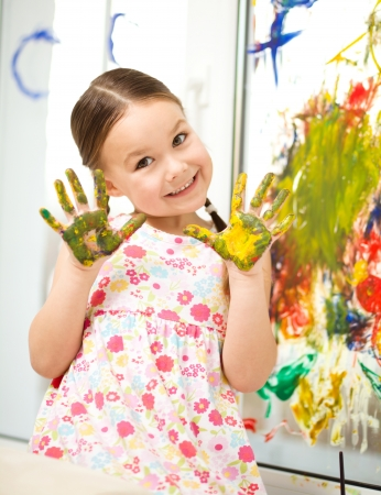 Portrait of a cute cheerful girl showing her hands painted in bright colors Stock Photo - 17134318