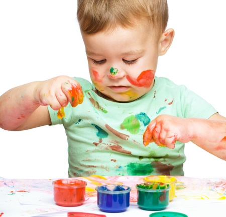 clenching fists: Portrait of a cute little boy playing with paints clenching his fists in joy, isolated over white Stock Photo