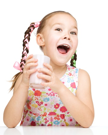 exhilarated: Cute little girl with a glass of milk, isolated over white
