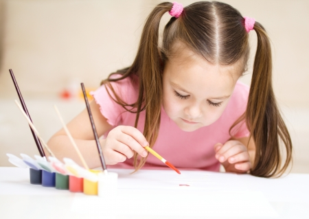 Cute cheerful child play with paints while sitting at\ table