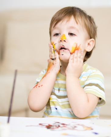 Portrait of a cute little boy messily playing with paints Stock Photo - 17190846