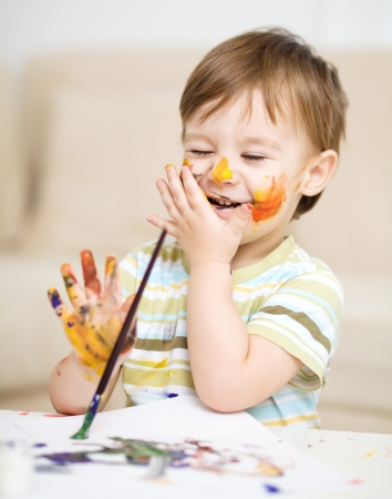 Portrait of a cute little boy messily playing with paints Stock Photo - 17190821