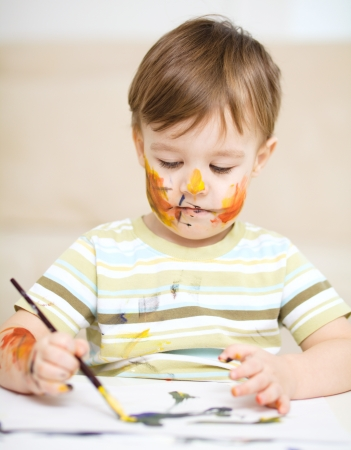 Portrait of a cute little boy messily playing with paints Stock Photo - 17190822