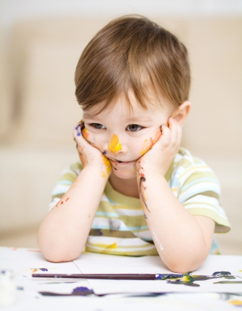 Portrait of a sad little boy messily playing with paints Stock Photo - 17190841