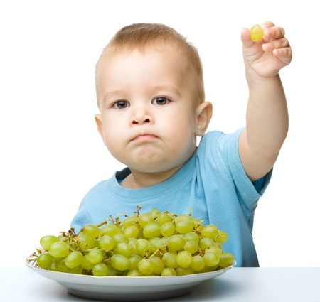 Little boy is eating grapes, isolated over white