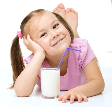 Cute little girl drinks milk using a drinking straw, isolated over white photo