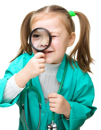 Cute little girl is playing doctor looking through magnifier, isolated over white Stock Photo - 17412184