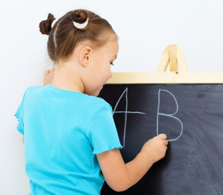 Little girl is writing letters on a blackboard photo