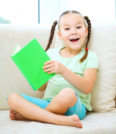 one story: Cute little girl is reading book while sitting on a couch, indoor shoot
