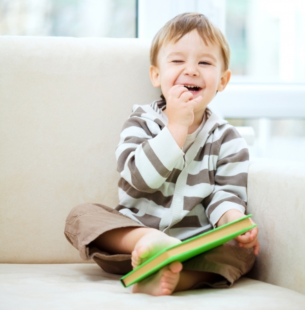 Little boy is reading book while sitting on couch, indoor shoot photo